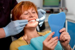 Smiling senior woman with new dentures sitting in the dental office and looking at the mirror